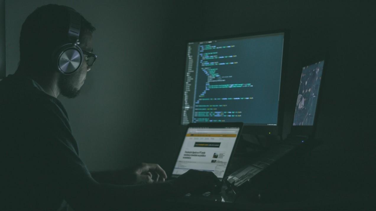 image of man looking at computer code three monitors automoderator automod moderating reddit