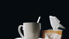 coronavirus vs flu image of coffee mug tissues bedside table influenza
