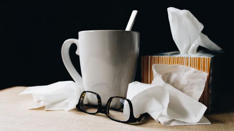 coronavirus vs flu image of coffee mug tissues bedside table influenza