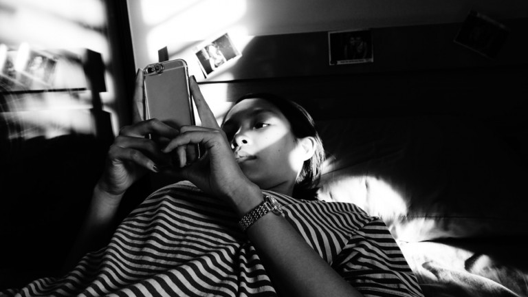 image of teen girl on bed looking at phone sexting sextortion