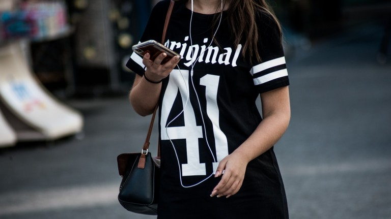 woman walking with iphone smartphone cell phone distracted texting app on street