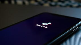 image of phone with tiktok logo on black background world health organization who joins coronavirus
