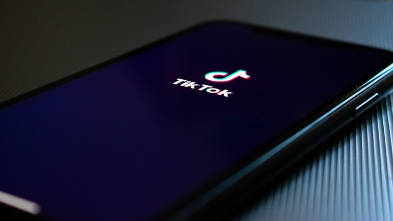 image of phone with tiktok logo on black background world health organization who joins coronavirus
