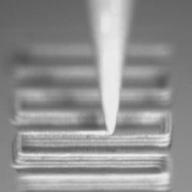 a nozzle depositing layers of electrode ink