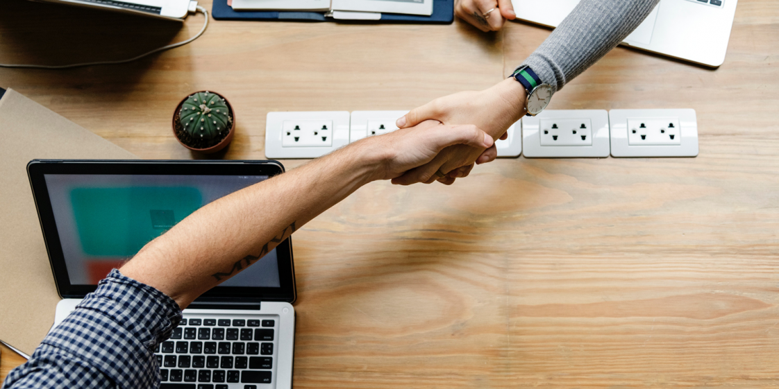 Image of two people shaking hands over a table next to a laptop.