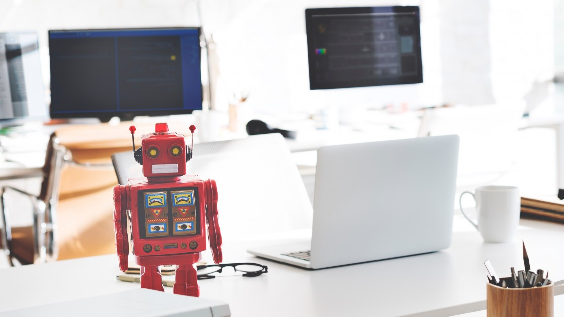 Image of a toy robot sitting on a desk next to a computer.