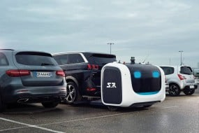 A robot picking up a 4x4 vehicle parked in a lot