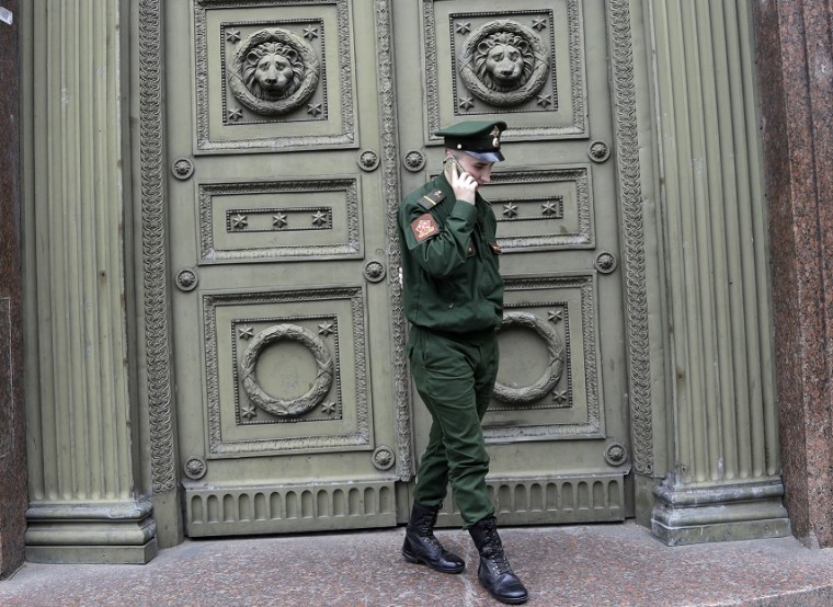 A Russian soldier in uniform talking on a smartphone