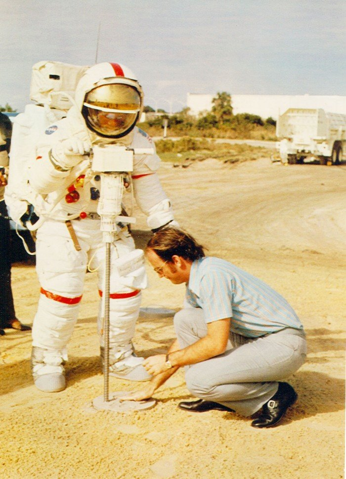 Photo of two men, one is wearing an astronaut suit