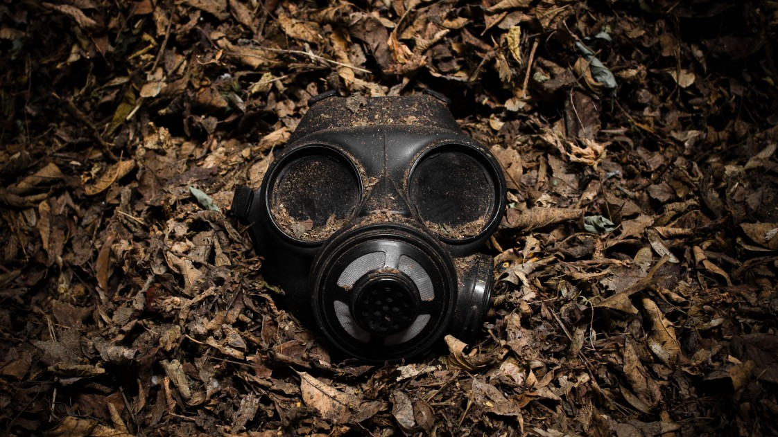 a gas mask in a bed of dry, brown leaves