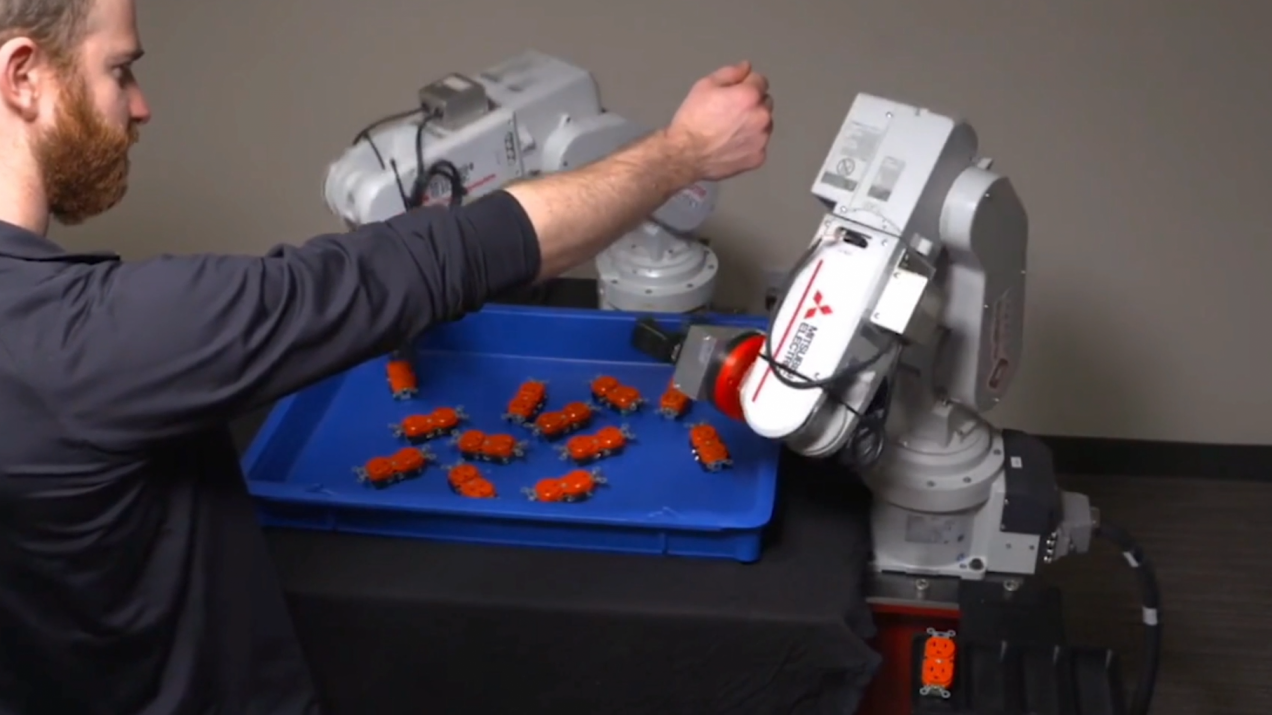 Photo of man holding out arm next to working robot arms