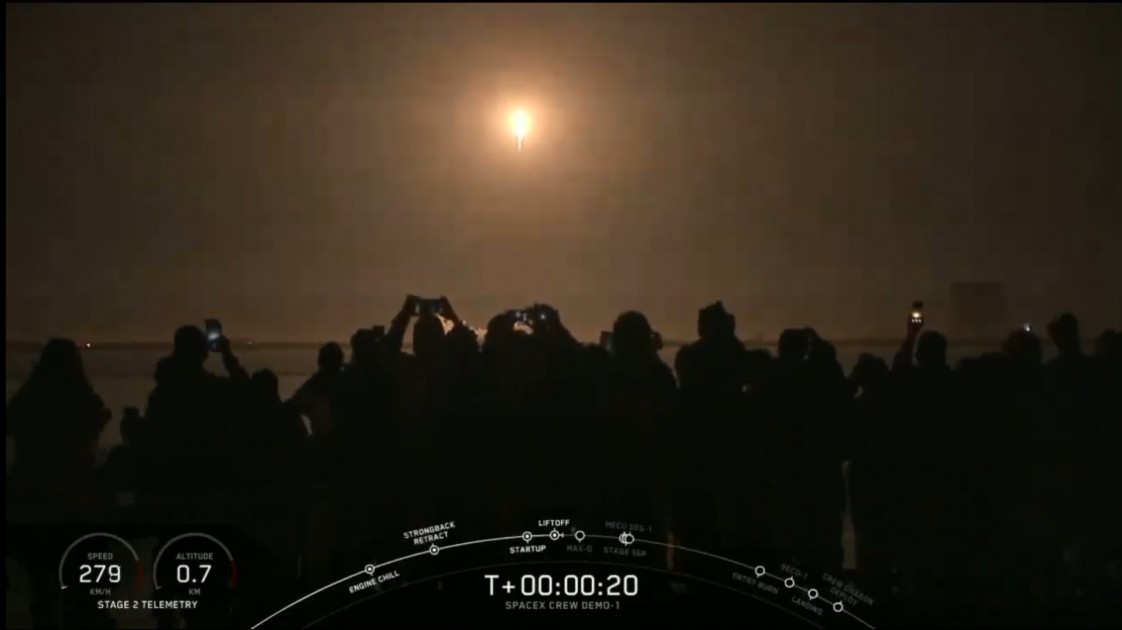 SpaceX's Falcon 9 rocket taking off at night with people watching.
