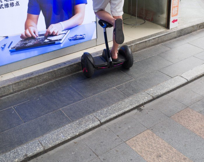 Photo of a man on a motorized scooter looking at a hardware advertisement