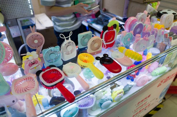 Photo of a vendor selling individual hand held fans of varying designs