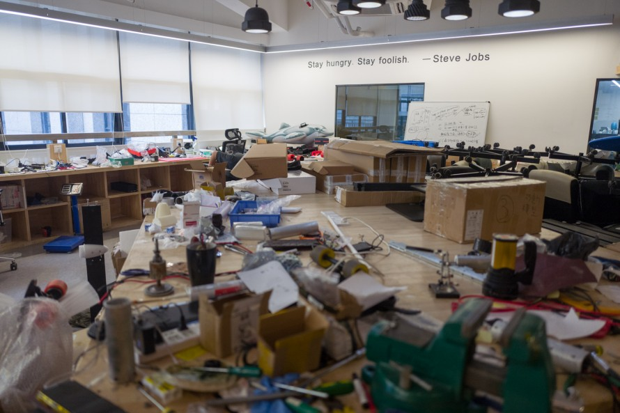 """Photograph of a messy maker space with a quote from Steve Jobs on the wall that reads """"Stay hungry, stay foolish"""""""