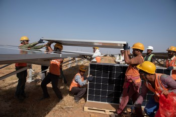 Photo of a group of men installing new solar panels
