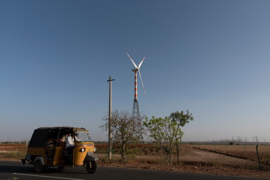 Photo of a wind turbine with a small vehicle in the foreground