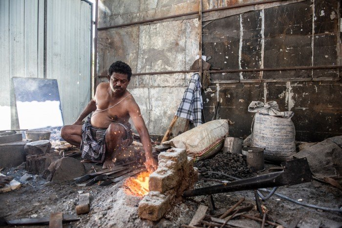 Photograph of Sidhappa Ji, a blacksmith who is using a solar-powered blower to stoke his fire