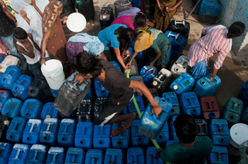 Image of a group of people trying to fill up blue water jugs with clean water