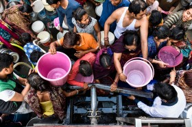 Image of people in India crowding to fill buckets with clean drinking water.
