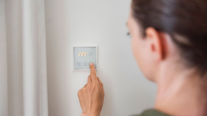 A woman using a smart thermostat in her home
