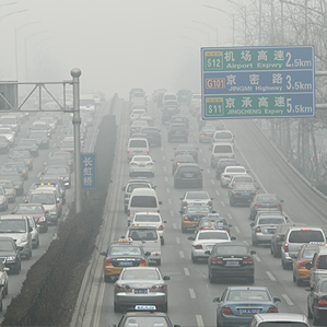cars travel on a road in heavy smog in Beijing, China