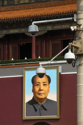 Photo of two surveillance cameras next to a portrait of Mao Zedong.