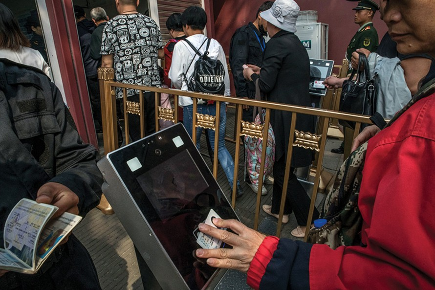 Photo of people tapping ID cards on a device before entering a building.