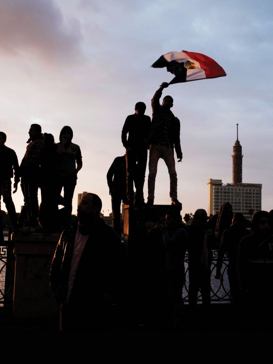 Photo of protester waving Egypt's flag.
