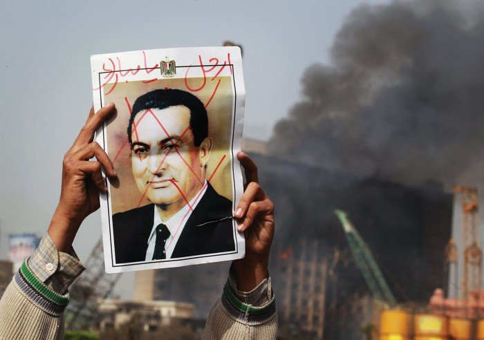 Photo of a protestor in Tahrir Square holding a photo showing President Mubarak's face crossed out