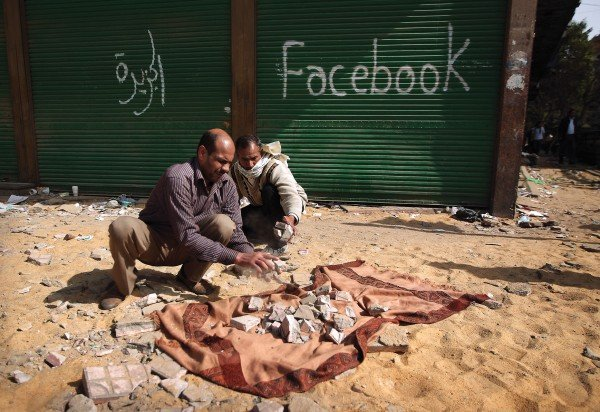 """Photo of two men breaking paving stones in Cairo, Egypt in front of a building with """"facebook"""" spray-painted on it"""