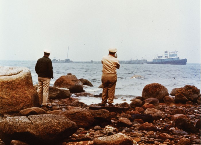 Image from 1969 showing US Coast Guard officers facing the ocean and oil barge Florida.