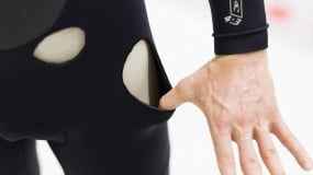 Photo of a swimmer in a wetsuit containing holes in the material.