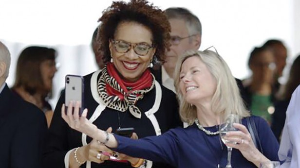 Photo of two women taking a selfie during a social gathering