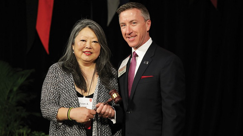 Photo of Outgoing Alumni Association president Hyun-A Park passing the ceremonial gavel to incoming president C.J. Whelan