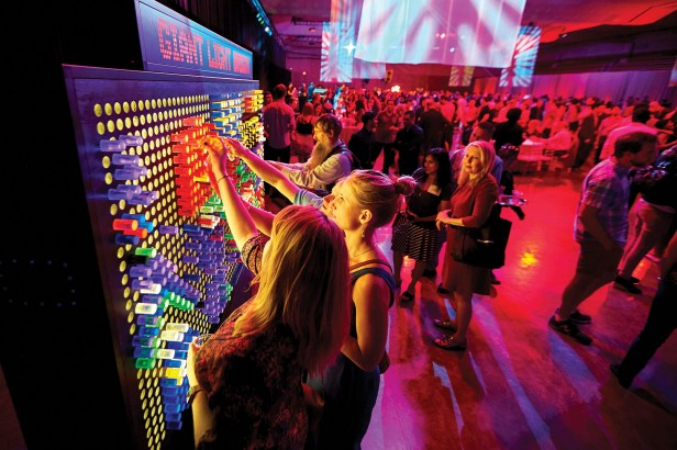 Photo of two people using a large Lite-Brite board in the forefront of a social gathering