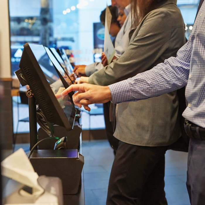 Photo of customers using Spyce's touchscreen menu-exploring and food-ordering computers