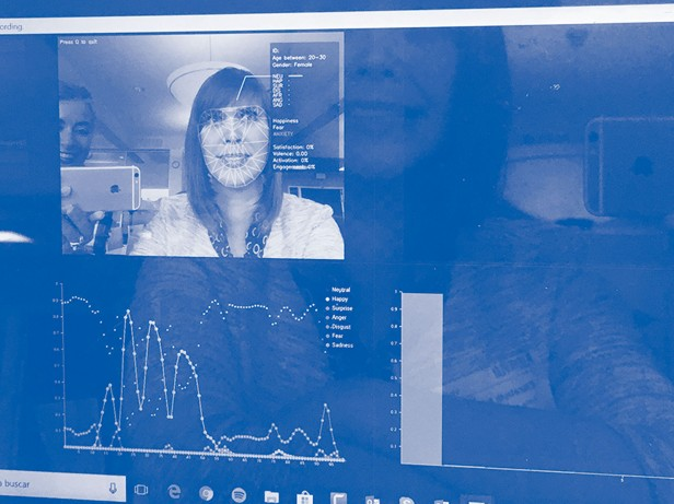 Photo of a computer screen. Windows on the screen show a graph and woman's face under facial recognition markers.