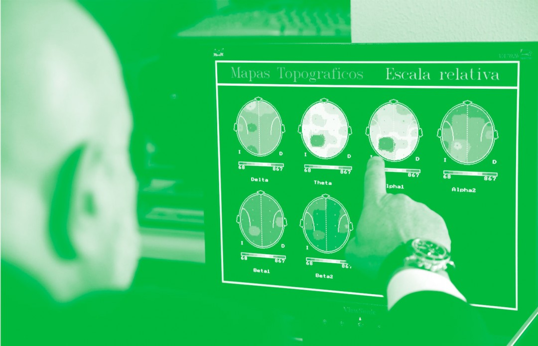 Photo of a man pointing at a computer screen showing brain activity maps.