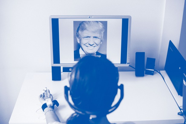 Photo of a woman wearing a monitor on her hand and headphones, looking at a computer screen displaying an image of Donald Trump.