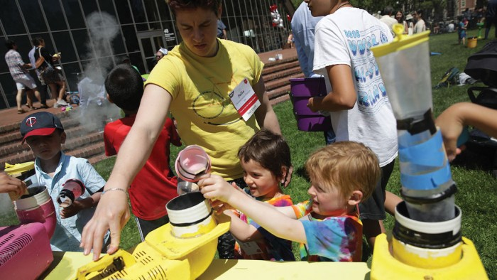 Young guests, with Julia Zimmerman Sharpe '09, experiment with smoke rings at the family maker fair at the Kresge Barbecue Pits.