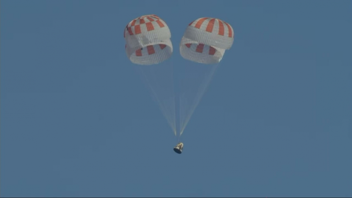 Image of SpaceX capsule floating down to the ocean.