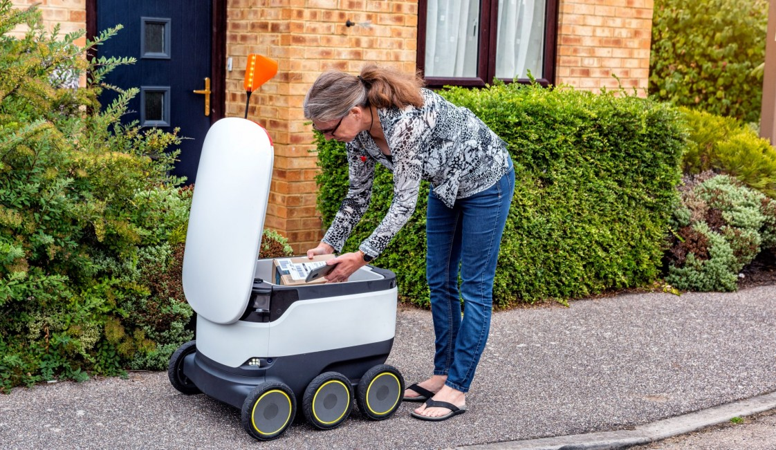 A woman taking a package out of a delivery robot