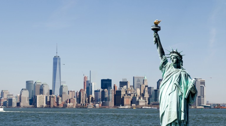 Photo of the statue of liberty with New York in the background