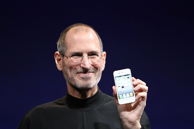 Steve Jobs holding white iPhone
