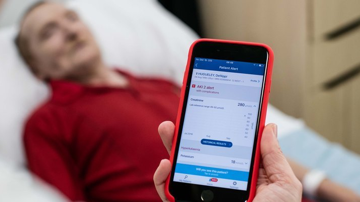 A man in a red polo top lying in a hospital bed behind a doctor holding up a smartphone
