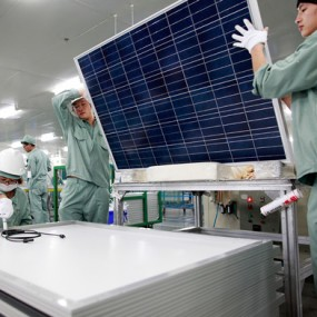 workers lift solar panel