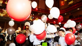 Photo of audience members at Symphony Hall catching falling baloons