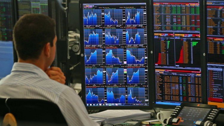 A trader sits in front of multiple screens