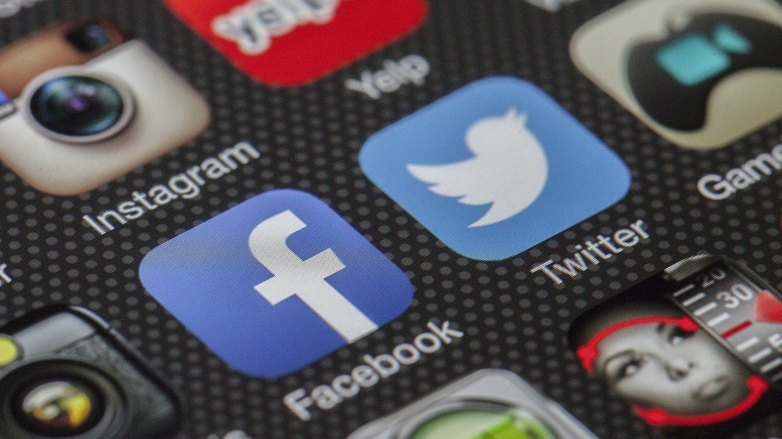 Image of a smartphone displaying the Facebook and Twitter apps.